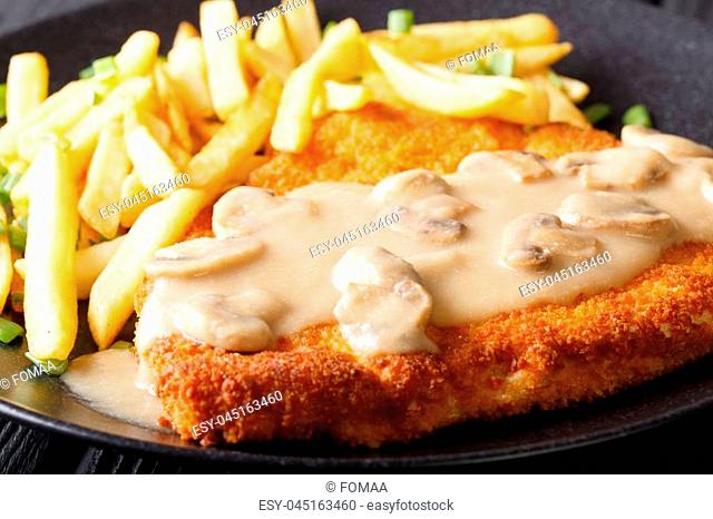 Jaeger schnitzel with French fries and mushrooms close-up on a plate. horizontal