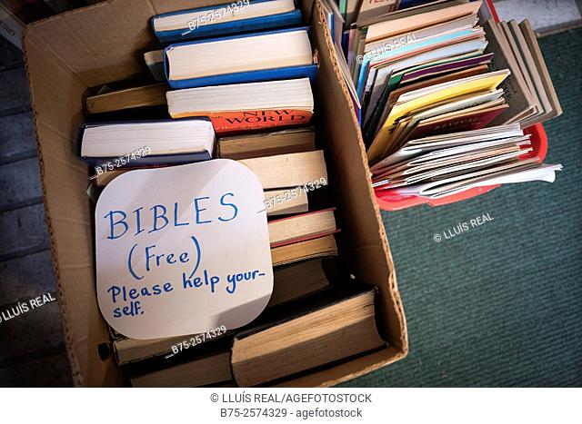Cardboard box full of bibles in a second hand book shop with a sign handwritten: Bibles, free, please help yourself. Settle, Yorkshire Dales, North Yorkshire