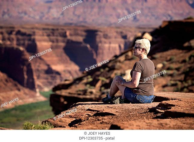 Woman sitting on the edge of a rock canyon cliff looking over the Colorado river with canyon walls in the background; Colorado, United States of America