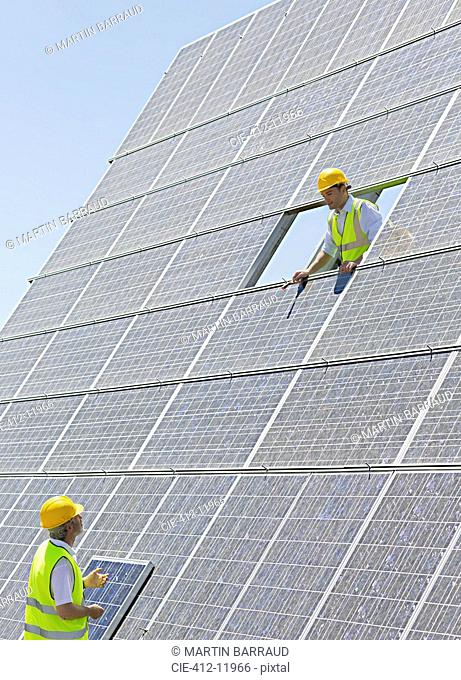 Workers examining solar panels