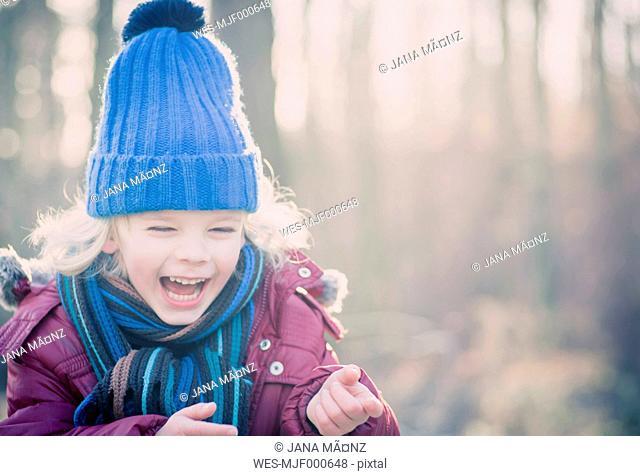 Laughing boy wearing blue woolly hat