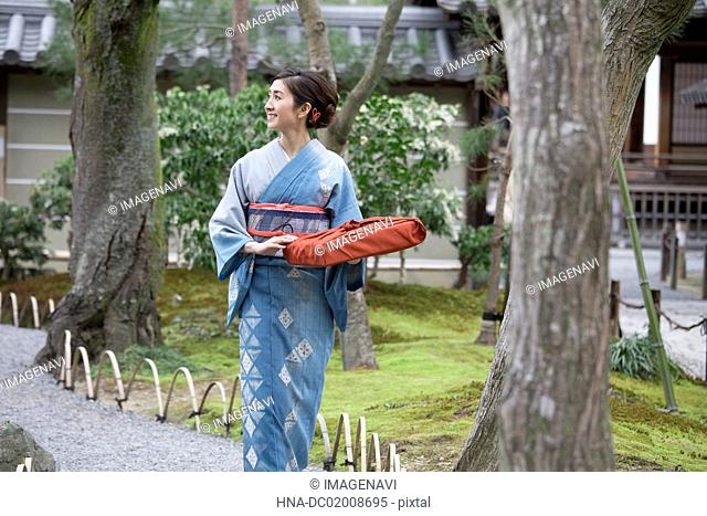 Young Japanese woman in kimono walking into Japanese garden
