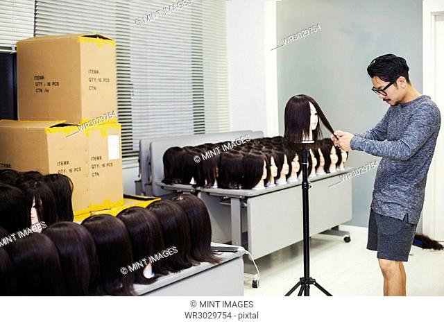Bearded man wearing glasses standing indoors, cutting hair of brown wig on mannequin head