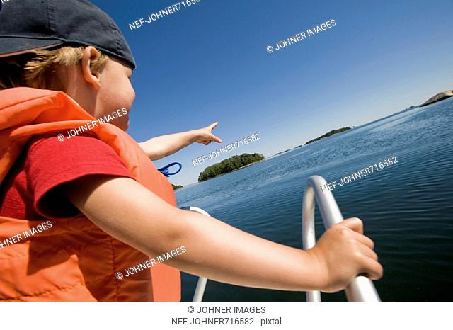 Boy in a motorboat pointing, Sweden