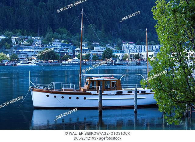 New Zealand, South Island, Otago, Queenstown, harbor view with boat, dusk
