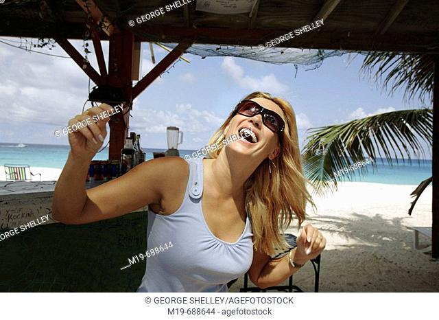 Girl listening and dancing to music at a tropical beach