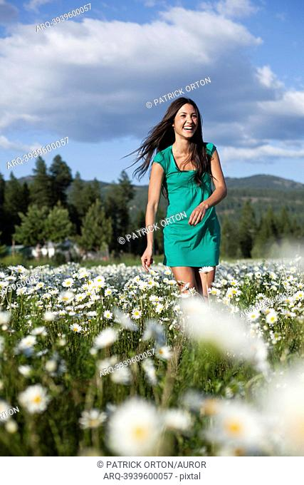 A young women laughs while dancing in a field of wild flowers