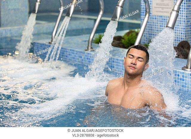 Horizontal indoors shot of handsome man with eyes closed resting under stream of shower in pool