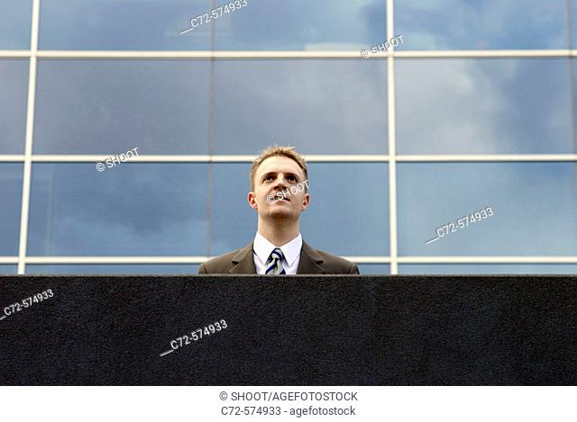 Business man outdoors in front of a modern office building