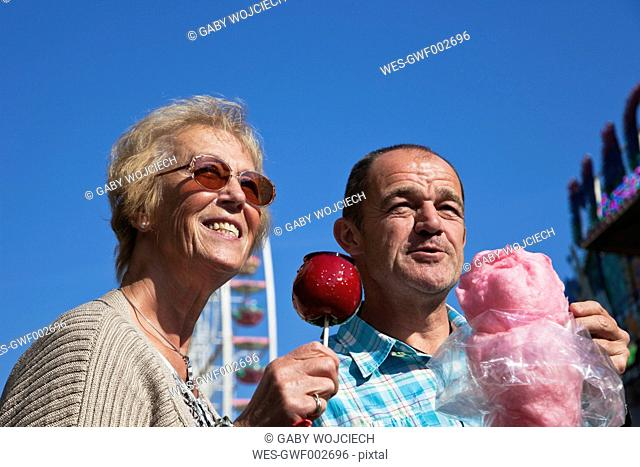 Man and woman on fair enjoying candied apple and cotton candy
