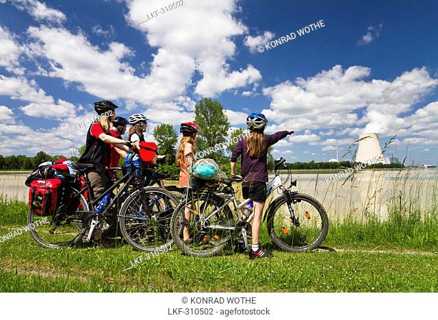 Cyclists looking over river Isar to Isar 1 Nuclear Power Plant, near Landshut, Isar Cycle Route, Lower Bavaria, Germany