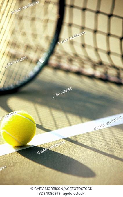 Tennis racket and ball next to net with shadows on court