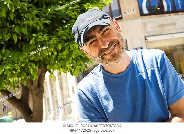 Middle-aged man with a beard and cap, in the center of the city, looking at the photographer tilted