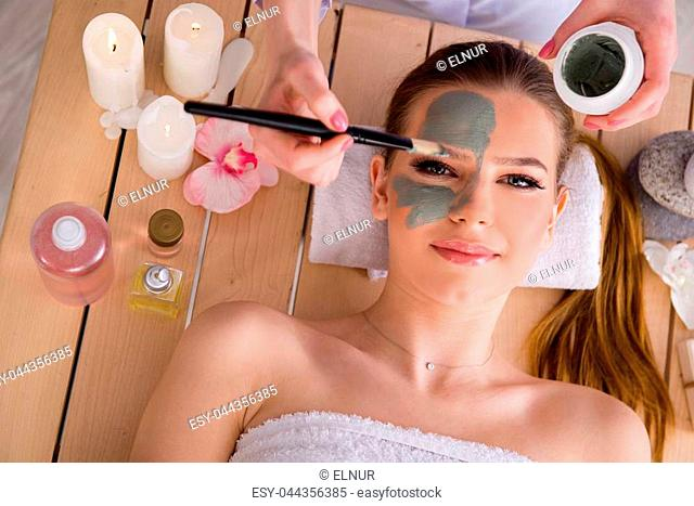 Young woman in spa health concept with face mask