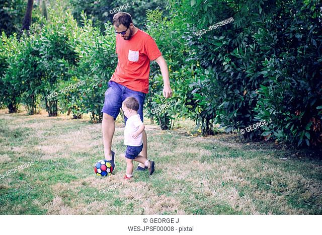 Father playing soccer with his little son on a meadow