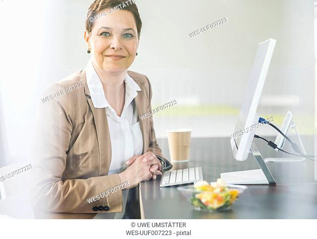 Female senior manager sitting in office, smiling