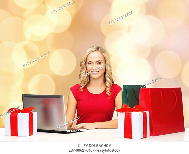 christmas, holidays, technology and people concept - smiling woman in red blank shirt with shopping bags, gifts and laptop computer over beige lights background