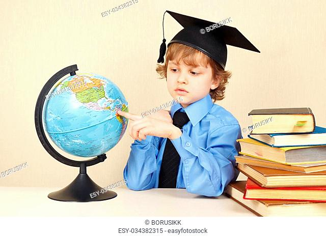 Little serious boy in academic hat showing on the globe among old books