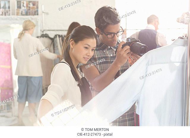 Photographer and fashion designer examining clothing