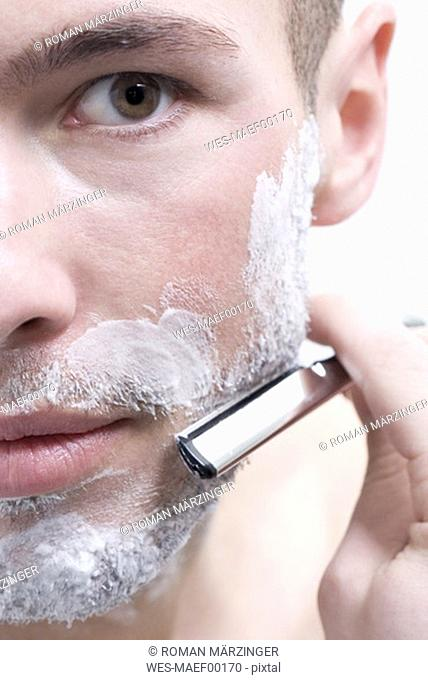 Man shaving with knife, detail