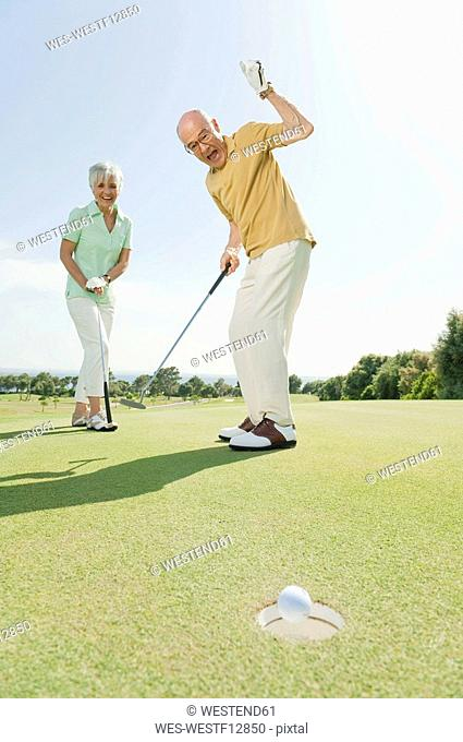 Spain, Mallorca, Senior couple on golf course, man cheering