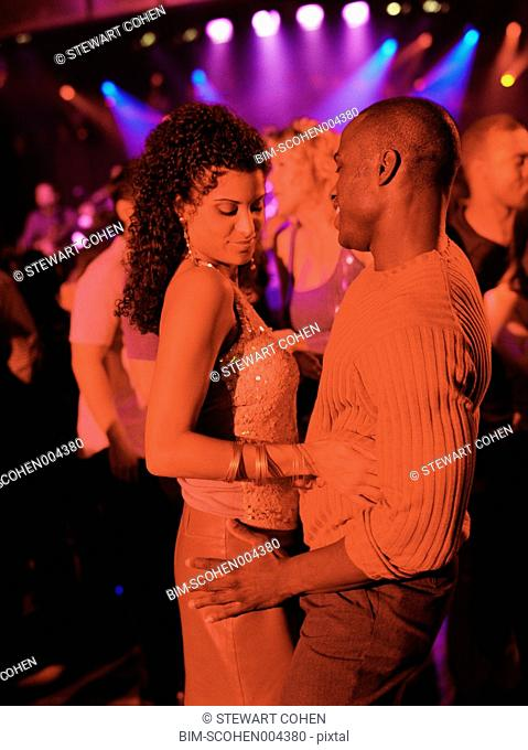 Young couple dancing together at club