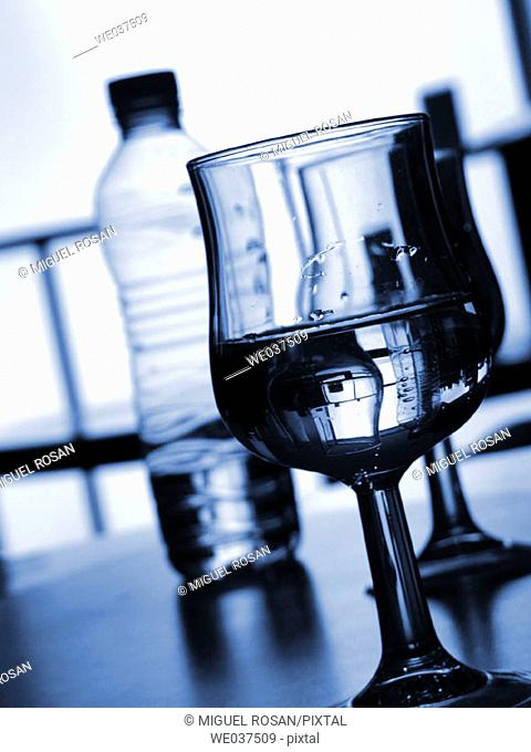 Inclined glass cup with a bottle of mineral water in the background out of focus