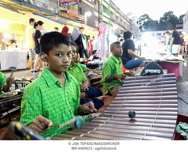 Group of children, Thais making music at the night market with xylophone, Krabi Town, Krabi Province, Thailand