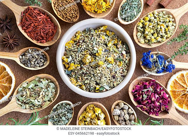 Mix of dried herbs on wooden spoons, top view. Horsetail, chamomile, cornflower, rose petals, nasturtium seeds, mullein, alchemilla, tilia, milk thistle seeds