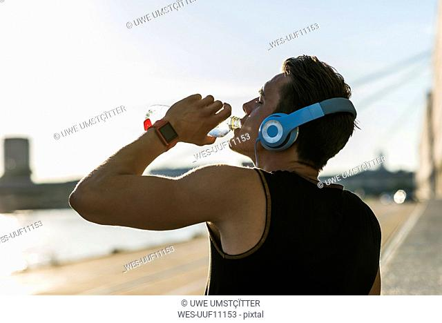 Young man wearing headphones, drinking water