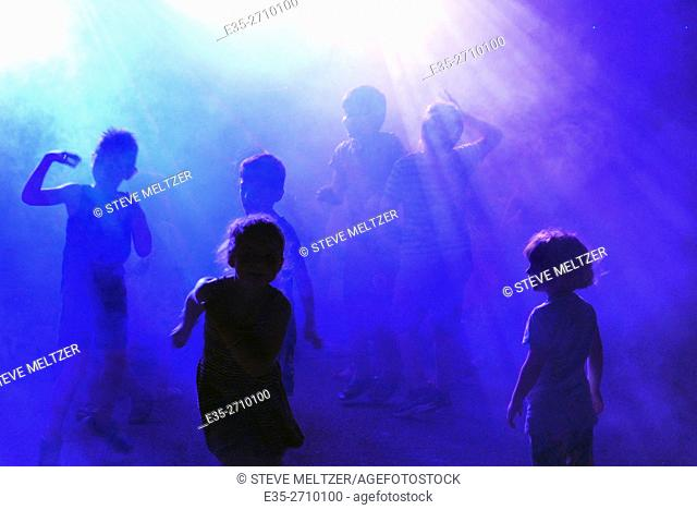 Children dancing in smoke and blue lights to music played by a disk jockey