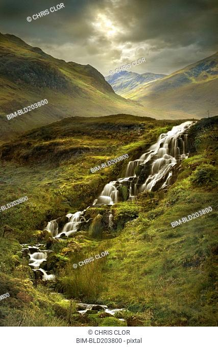 Creek flowing over rocks in rural landscape