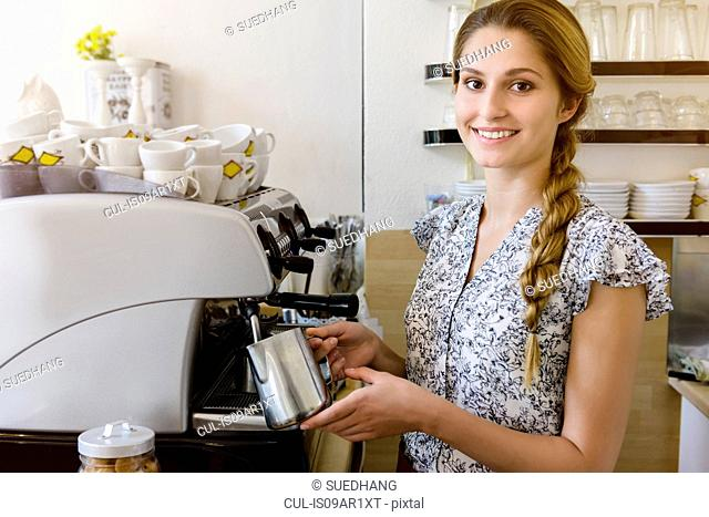 Young woman using coffee maker looking at camera, portrait