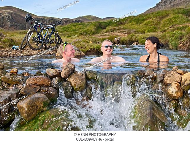 Low angle view of three mountain bikers bathing in hot river, Reykjadalur valley, South West Iceland