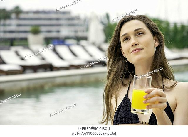 Woman drinking juice next to swimming pool