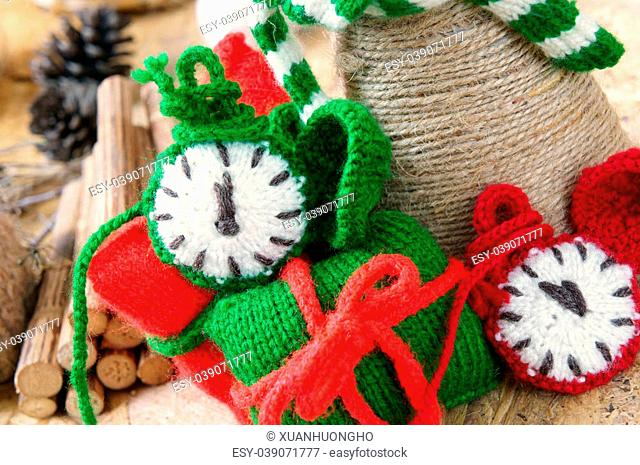 Amazing christmas background, handmade clock in red and green color, colour of xmas seasonal, ornament for winter holiday with knitted watch, gift, pine cone