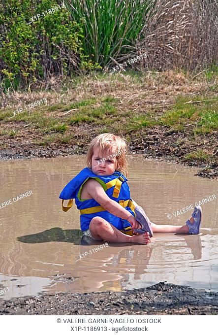 This cute 18 month old Caucasian toddler girl is sitting in her diaper and life vest in a mud puddle and playing as she's taking off her sandal Great classic...