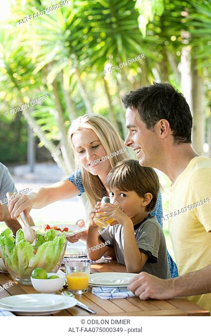 Parents and young son having breakfast outdoors