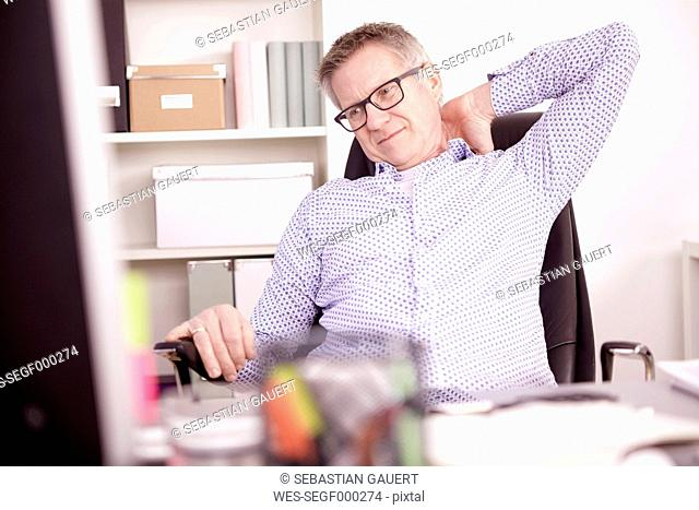Businessman with neck pain at home office