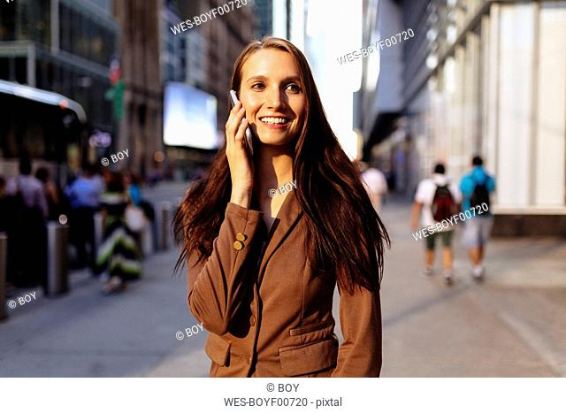 USA, New York, Manhattan, smiling young businesswoman on the phone