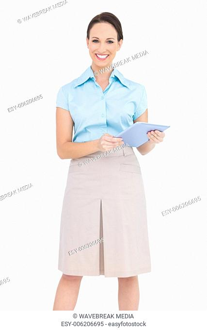 Happy young businesswoman holding tablet pc