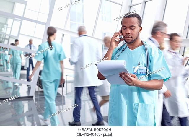 Male surgeon with clipboard talking on cell phone in hospital lobby