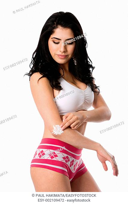 Beautiful young woman applying exfoliating moisturizing cream on dry elbow skin, isolated