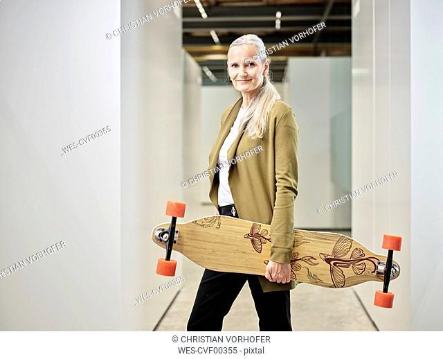Portrait of businesswoman carrying longboard on office floor
