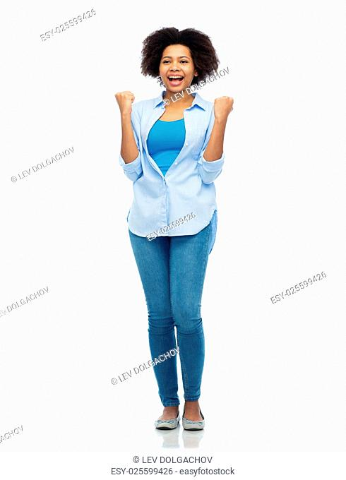 people, success and portrait concept - happy african american young woman with raised fists celebrating victory over white
