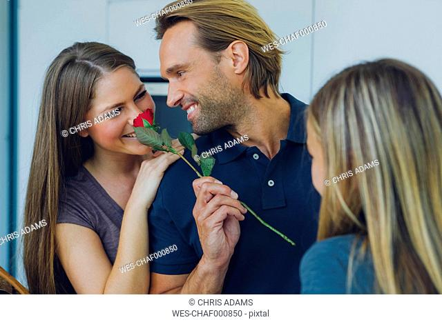 Smiling couple with red rose and daughter
