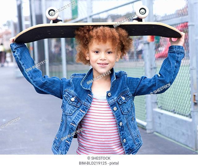 Girl holding skateboard in urban park