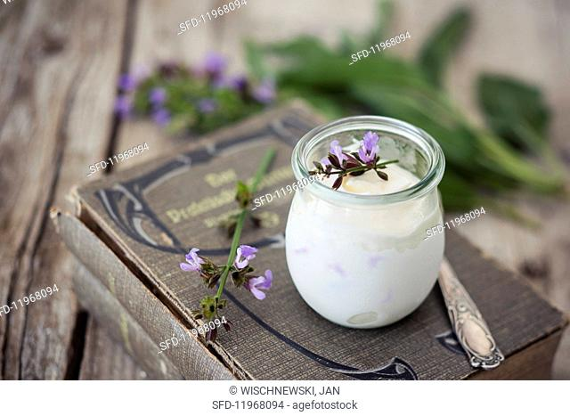 Ice cream parfait made from sage flowers in a glass on an old gardening book