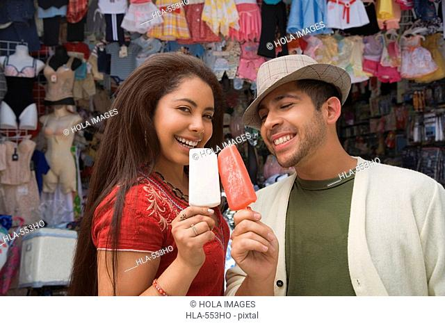 Portrait of a young couple holding ice creams and smiling