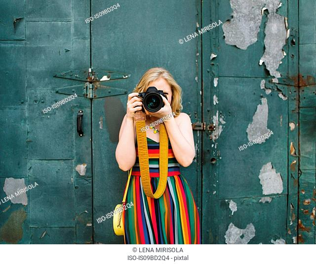 Young woman in striped dress in front of industrial door taking photographs, portrait